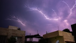Lightning bolts of approaching thunderstorm over residential buildings.