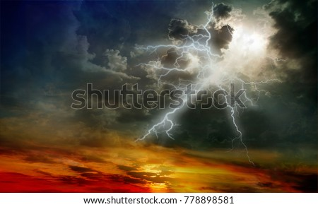 Lightning during a thunderstorm on a sunset background