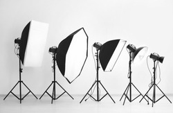 Lightning equipment near white wall in photo studio