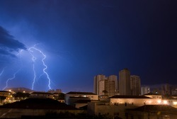 Lightning in the blue sky of the city of Santos.