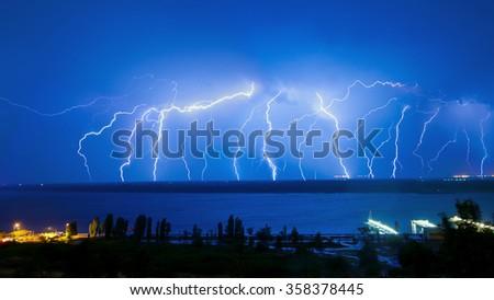 Lightning over night river in the blue sky #358378445