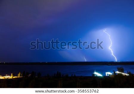 Lightning over night river in the blue sky #358553762