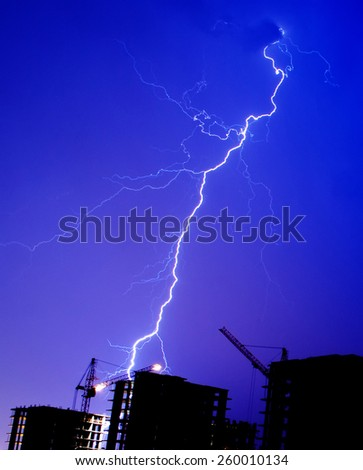 Lightning storm crane weather industrial city building construction night flash