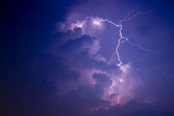 Lightning streaks lights up clouds in the middle of the night.Night scene.