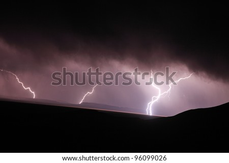 Lightning strike in the darkness over mountains