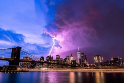 Lightning strike through New York City from Brooklyn bridge perspective.