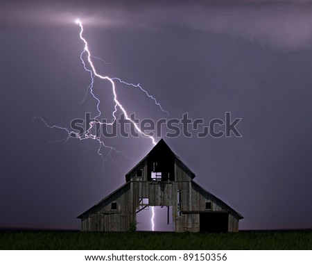 Lightning striking the ground behind a barn.