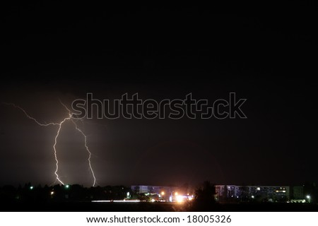 Lightning stroke in storm weather on city suburb