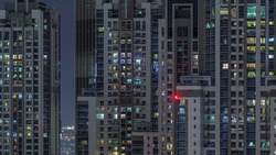 Lights from windows of offices and apartments aerial timelapse. Skyscrapers with working people in the evening in Business Bay, Dubai, United Arab Emirates. Complex of towers at night