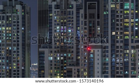 Photo of  Lights from windows of offices and apartments aerial timelapse. Skyscrapers with working people in the evening in Business Bay, Dubai, United Arab Emirates. Complex of towers at night
