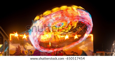 Lights going around on a carnival ride create red streaks