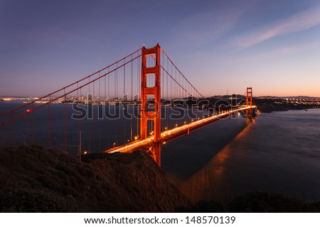 Lights illuminate the Golden Gate Bridge and city skyline at twilight in San Francisco aerial view from north side cliffs