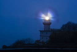 Lights in the lighthouse with fog at dawn, Igueldo, city of Donostia (San Sebastian)