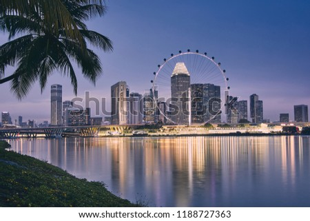 Lights of modern asian city. Palm tree against Singapore skyline at dusk.  #1188727363
