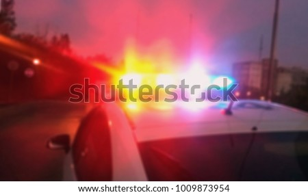 Lights of police car in evening time. Patrolling the city, crime scene. Abstract blurry image.