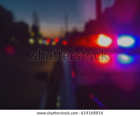 Lights of police car in night time. Night patrolling the city. Abstract blurry image.