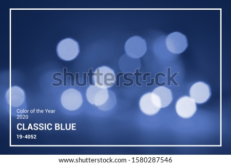 Lights on blue defocus background. Bokeh defocus disco effect. Holiday abstract background christmas lights garland. Winter festive glitter macro concept in trendy classic blue color of the year 2020 #1580287546
