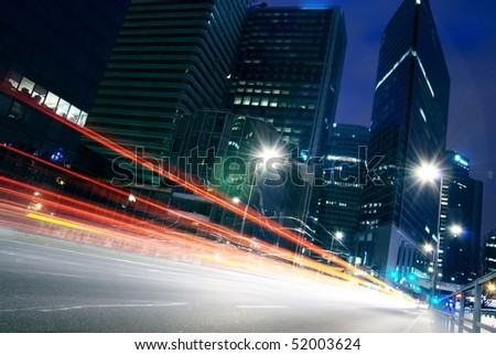 lights trails of cars in building centre - stock photo