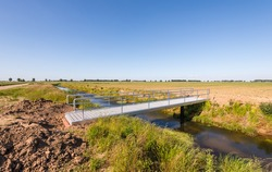 Lightweight aluminum bridge built over the water in an agricultural landscape.