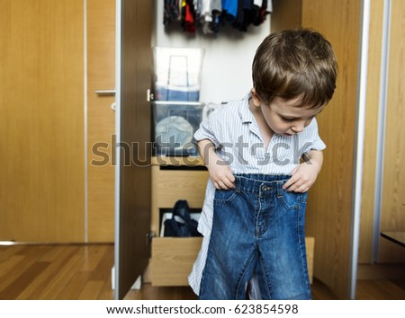 Liitle boy dressing and wearing his pants by himself