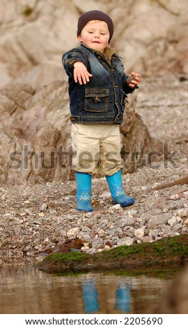 liitle boy throwing stones in a rock pool on a beach