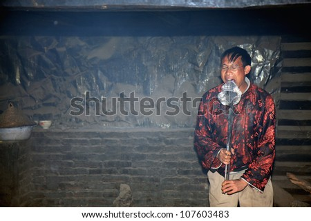 LIJIANG, CHINA - DECEMBER 8, 2010: A Naxi ethnic man presses a hot metal plate onto his tongue at the Dongba Valley Cultural Village, on December 8, 2010 in Lijiang, Yunnan Province of China.