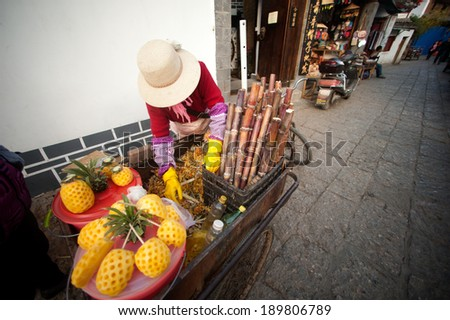 Lijiang,China � March 15 : Chinese woman at a Rickshaw loaded with fruit in Lijiang is the largest ancient old town on March 15, 2014 in China,Lijiang city,Yunnan province in Southwestern of China.
