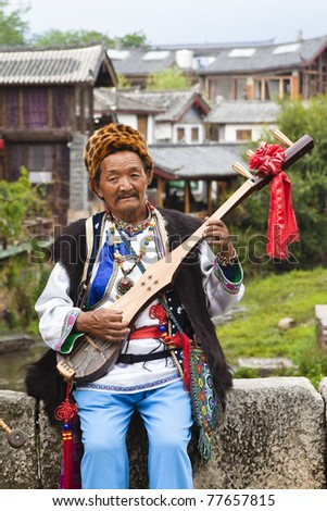 LIJIANG - JUNE 27: Unknown naxi musician in traditional costume playing a music instrument in the ancient town June 27, 2009 in Lijiang, Yunnan Province, China.