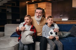 Likable concentrated senior bearded grandfather with his cheerful 10-15s grandsons spending their free time at revision the basketball game on tv