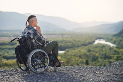 Likable incapacitated young guy sitting alone in wheelchair on the hill on beautiful nature background and praying.