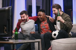 Likable joyful multiracial young guys cheering their favourite football team with screams and hands up during watching sport game on tv