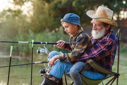 Likable respected 70-aged bearded grandfather holding on knees 10-aged cute grandson and teaching him to catch fish.