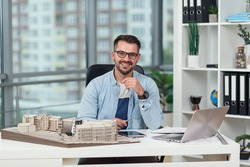 Likable smiling successful bearded 35-aged architect in glasses sits at his workplace with mock-up of future buildings.