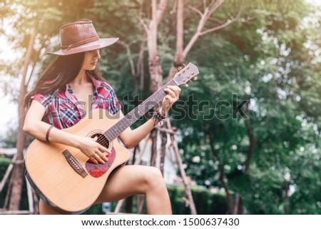 Like a country star. Beautiful cowgirl playing guitar. Copy space on the right side