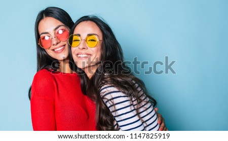 Like a sisters! Two beautiful young girl friends in sunglasses posing with smile and have a fun on blue background