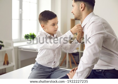 Like father like son. Young man and his serious little kid dressing up and putting on white shirts. Dad and child are getting ready to wear suits or tuxedos for an event or special family occasion