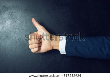 Like this. Close-up of human hand with thumb up in front of the blackboard #517252924