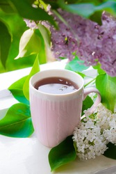 Lilac and tea . Hot drink. Summer flowers. The evening Cup of tea.