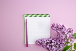 Lilac branch and Notepad on a pink background. notebook with bright lilac. Postcard for loved ones, relatives, friends and colleagues. Spring background. Holiday card. Top view with copyspace