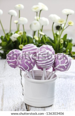Lilac cake pops in white ceramic jar. White daisies in the background. Party table setting.