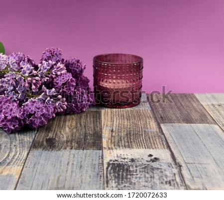 Lilac decoration stock images. Lilac on a wooden background. Bunch of syringa images. Lilac and candle images. Aromatic spa still life. Lilac flower frame stock images. Bouquet of lilacs on the table