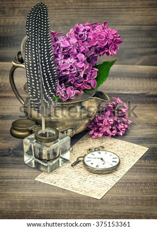 Lilac flowers and antique inkwell on wooden background. Vintage style toned picture #375153361
