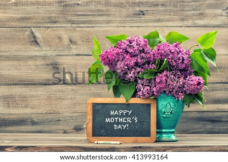 Lilac flowers and vintage blackboard with sample text Happy Mothers Day! Vintage style toned picture. Mother\'s Day greetings card. Vintage still life. Mother\'s day. Mothers Day gift. Mothers Day
