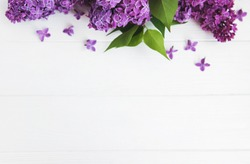 Lilac flowers on a white wooden background