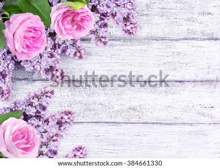 Lilac flowers with roses on background of shabby wooden planks