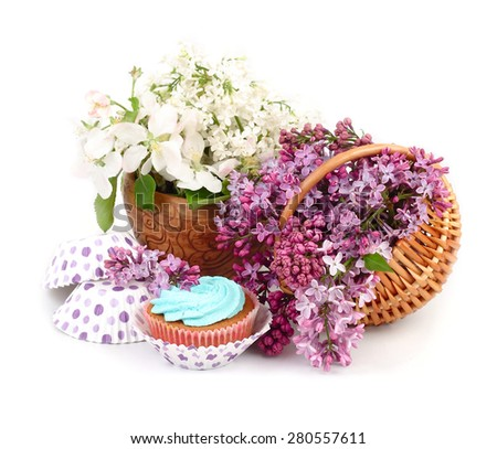 Lilac in a basket and cake on a white background.