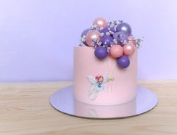 Lilac-pink festive beautiful cake with balloons and a girl.