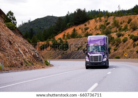 Lilac semi truck with aluminum trailer is moving on the turn along winding highway through the Grand pass in California against the orange sandstone slopes transporting cargo to destination warehouse #660736711