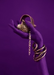 Lilac woman's hand with gold jewelry. Oriental Bracelets on a magenta painted hand. Gold Jewelry and luxury accessories, neon background closeup. High Fashion art concept