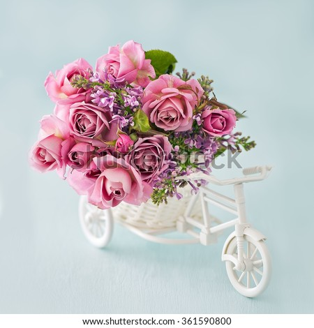 Lilacs and pink roses flowers in a decorative white wooden bicycle on a blue background .Floral gift for a wedding or birthday. #361590800